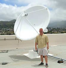 Man standing in front of satellite dish