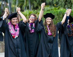 three law students in graduation attire holding their hands up