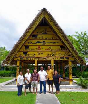 Members of UH delegation stand in front of the Mesekiu Bai (meeting house), Palau Community College with President Patrick Tellei (center right), Koror, Palau