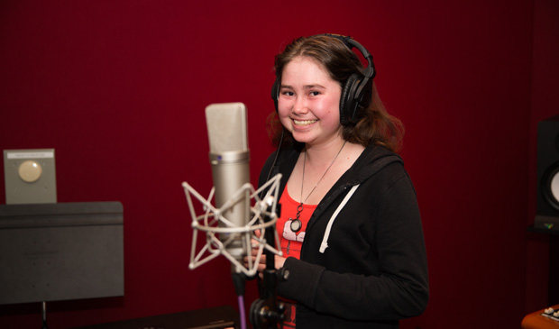 Make-a-Wish teen Skyla stands in front of a microphone