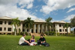 Students sitting on the lawn in front of Hawaii Hall