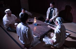 Cast members in a meeting scene