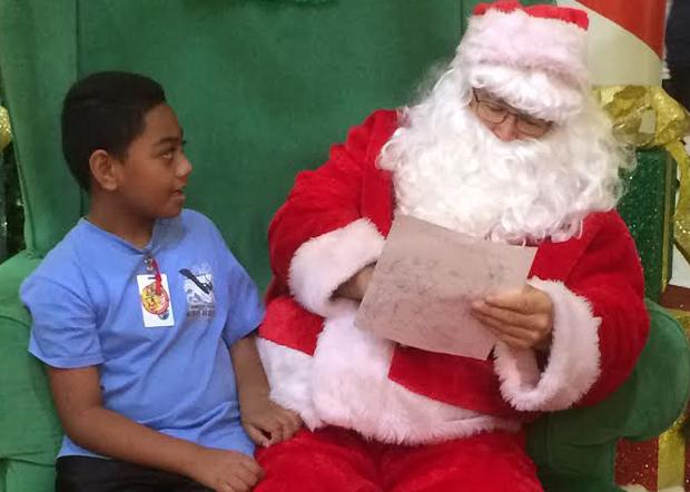 Santa reading a Christmas wish list