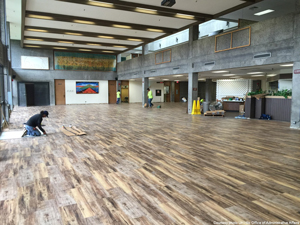 Work crew puts the finishing touches on the new rustic looking floor of the Campus Center Dining Room