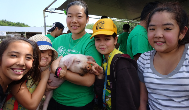 Children pose with a piglet