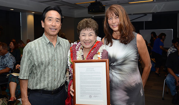 Vice Chair Benjamin Asa Kudo, left, and Chair Jan Naoe Sullivan, right, present Doris Ching with her resolution