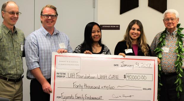 five people holding big check