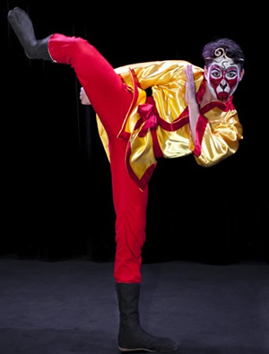 actor in bright red Monkey costume with mask in a one legged pose