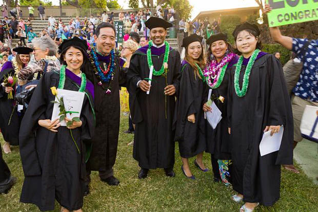 L L M graduates in regalia outside with lei