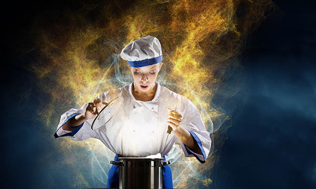Chef in hat and apron while doing magic above pot