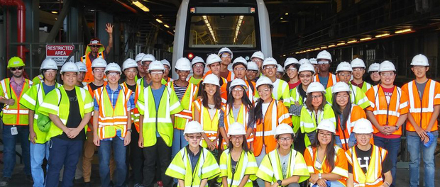 group Summer Engineering Students pose in front of a rail car