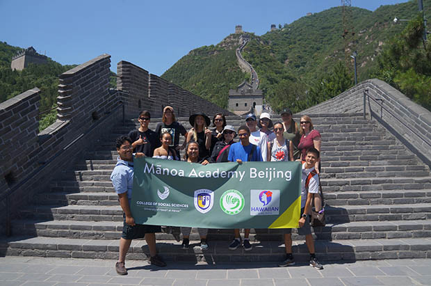 Manoa Academy Beijing students holding a banner at the Great Wall of China