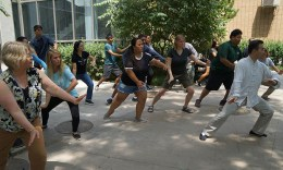 Students practicing tai chi outside in courtyard.