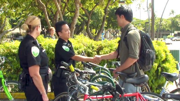 two campus security officers shaking hands with a student
