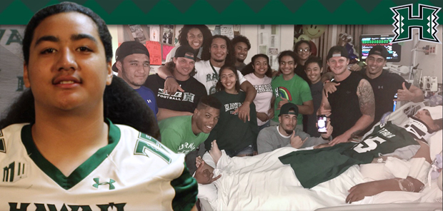 Naotala lying in a hospital bed surrounded by the rest of the football team visiting him
