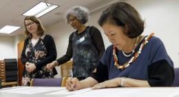 Irene Inouye signing a paper