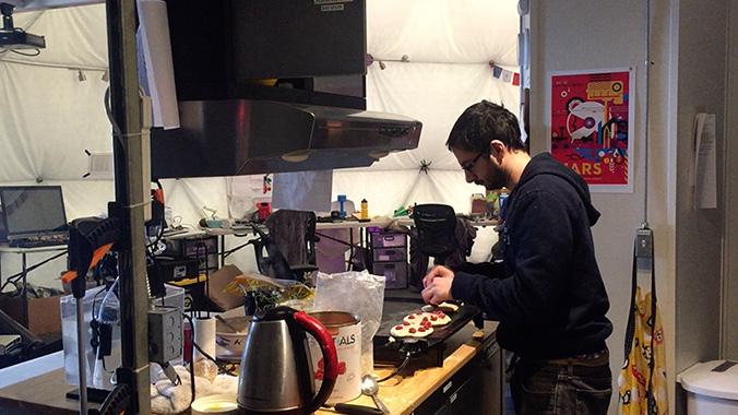 A crewmember prepares pancakes on the HI-SEAS habitat kitchen equipment