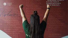 Back of a teacher with outstretched arms in front of a wall of Hawaiian language
