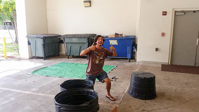 Student giving double thumbs up with trash containers