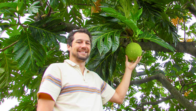 Lincoln holding a breadfruit hanging from a tree