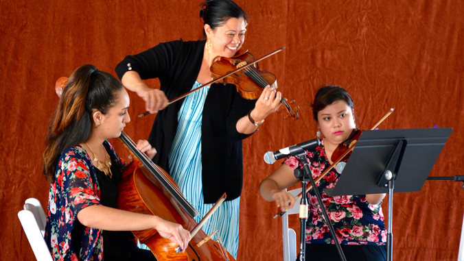 three people playing musical instruments