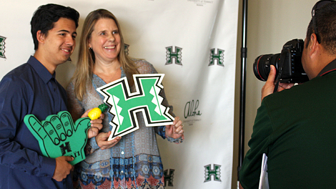 2 people having their photo taken with UH Manoa logo