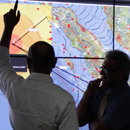 two researchers studying a map