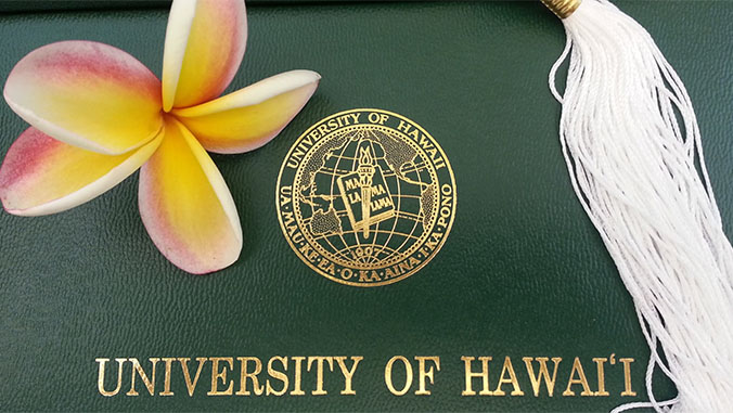 Cover of a U H Manoa diploma with a white tassel and plumeria