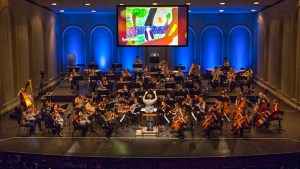Wide shot of the symphony performing with animation on a screen above the stage