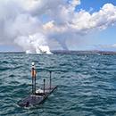 autonomous robots in the ocean with volcanic gas plumes in the background, Credit: Liquid Robotics