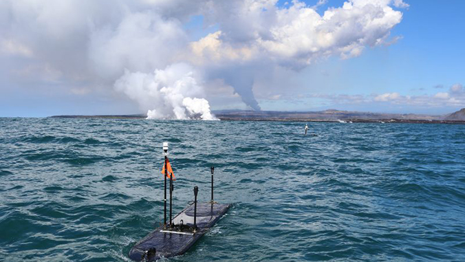 autonomous robots in the ocean with volcanic gas plumes in the background