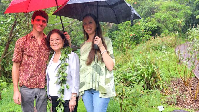 three people under umbrellas in the rain at the arboretum