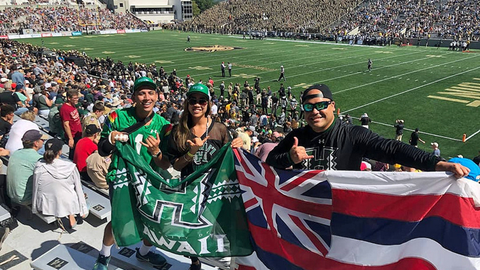two people holding UH athletics flag and one person holding Hawaiian flag at West Point stadium