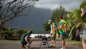 Three people standing around a landed drone, click for larger image