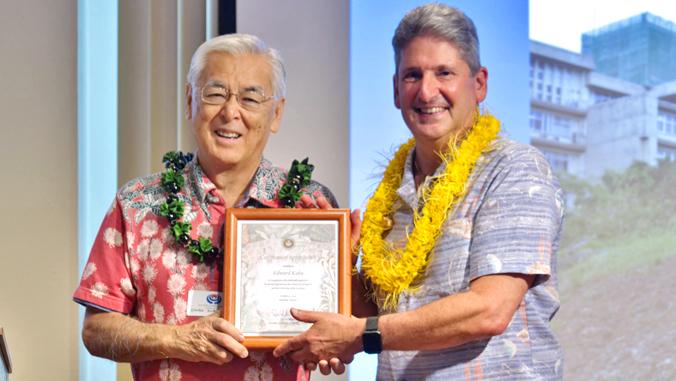 two men holding framed certificate