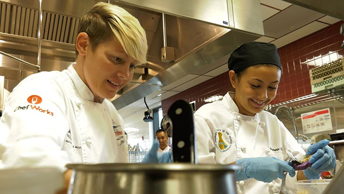 Two culinary students working in a kitchen