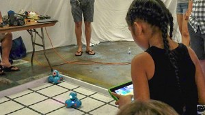 Girl controlling small robots with a tablet, click for larger image