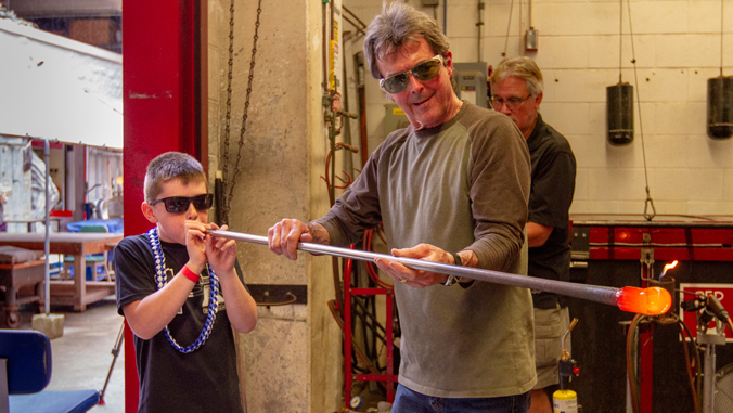 boy blowing in metal tube with hot glass on the end