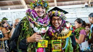 two student in graduation regalia and lei