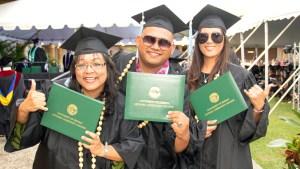 students in graduation regalia holding diploma