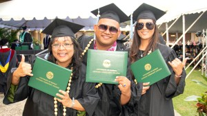 students in graduation regalia holding diploma