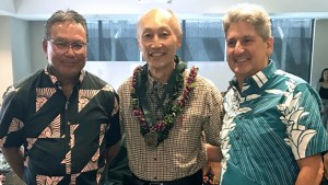 three people, one holding award and wearing lei