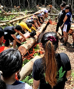 C O P students rolling a log