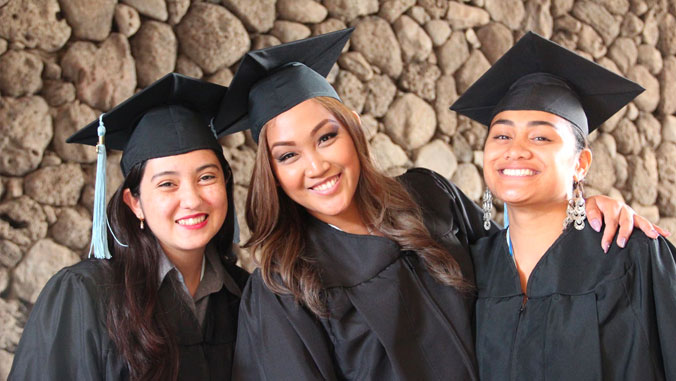 3 community college graduates in cap and gown