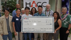 Team holding a check with Governor Ige