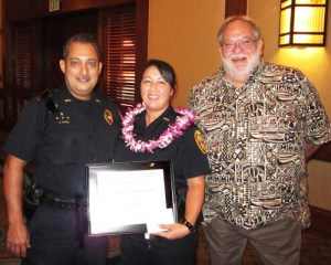 "Lieutenant Juergen Canda and Randy Crowe, president of the Hawaii Island Safety and Security Professionals Association, present a ""Kohala Officer of the Quarter"" award to Community Policing Officer Kristi Crivello."