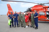 Coast Guard and Hawaii Fire Department personnel stand with the mother of Sidney Uemoto following her daughter's rescue nine miles off Kona, Hawaii, July 15, 2016. Uemoto and David McMahon were both rescued by a Coast Guard MH-65 Dolphin helicopter crew following an expansive joint search by Navy, Royal New Zealand air force, U.S. Air Force and Coast Guard crews. (U.S. Coast Guard photo)