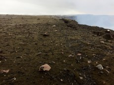 This view shows the main body of the tephra deposit, which comprises the dark fragments scattered from the foreground to the web camera in the background (the HTcam thermal webcam). The rim of Halemaʻumaʻu is to the right; the closed overlook is behind the photographer. Photo taken Monday, November 28, 2016 courtesy of USGS/HVO
