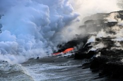 A close-up of one of several streams of lava entering the ocean at the front of the Kamokuna lava delta on Kīlauea's south flank. The billowy white plume formed by the interaction of hot lava and seawater may look harmless, but it is a mixture of superheated steam, hydrochloric acid, and tiny shards of volcanic glass—all of which should be avoided. Photo taken Wednesday, November 30, 2016 courtesy of USGS/HVO