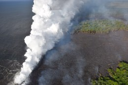 """Late last night, the fissure 20 lava flow reached the ocean. Hot lava entering the ocean creates a dense white plume called """"laze"""" (short for """"lava haze""""). Laze is formed as hot lava boils seawater to dryness. The process leads to a series of chemical reactions that result in the formation of a billowing white cloud composed of a mixture of condensed seawater steam, hydrochloric acid gas, and tiny shards of volcanic glass. This mixture has the stinging and corrosive properties of dilute battery acid, and should be avoided. Because laze can be blown downwind, its corrosive effects can extend far beyond the actual ocean entry area. Photo taken Sunday, May 20, 2018 courtesy of U.S. Geological Survey"""